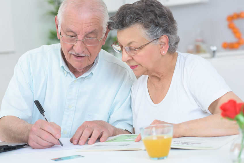 Elderly couple looking at disability list and taking notes