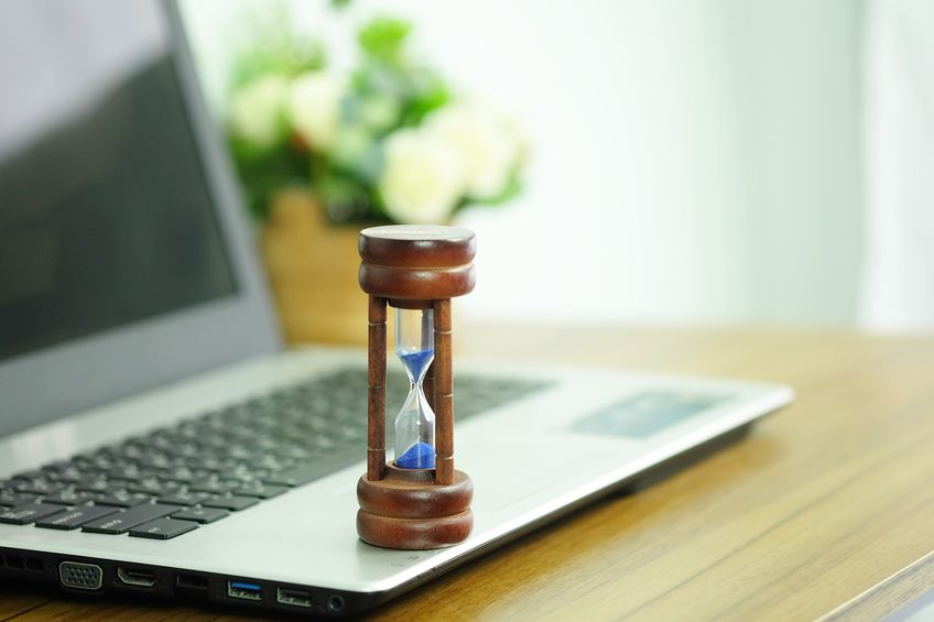 Wooden hourglass on a laptop computer, Managing time and countdown to deadline concept.